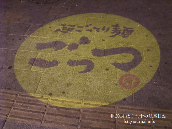 夜になると店前の路面にロゴが浮かぶ[超ごってり麺ごっつ]